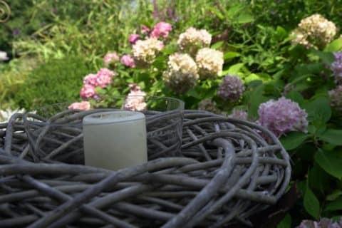 Dekokerze vor Gebüsch mit Blumen