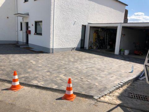 Helles Haus mit gepflasterter einfahrt und Garage