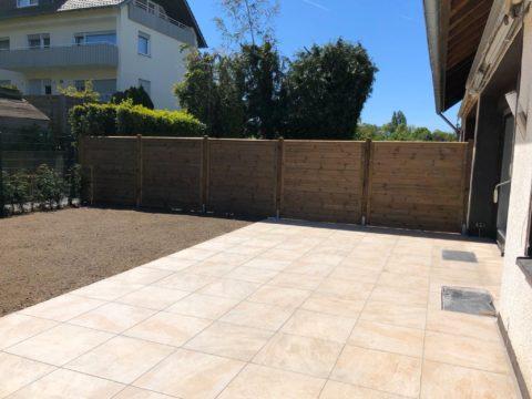 Terrasse mit hellen Fliesen und Zaun