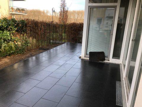 Terrasse mit dunklen Fliesen und Hecke