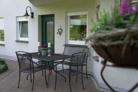 Terrasse mit Tisch und Stühlen.