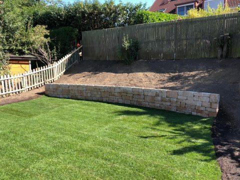 Bruchsteinmauer in Garten mit Rollrasen