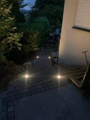 Beleuchtete Gartentreppe mit Pflasterelementen führt zum Garten