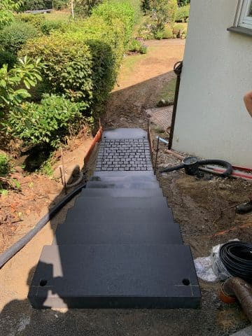 Gartentreppe mit Pflasterelementen führt zum Garten