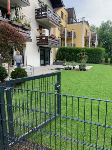 Grauer Gartenzaun begrenzt den neuen Rollrasen