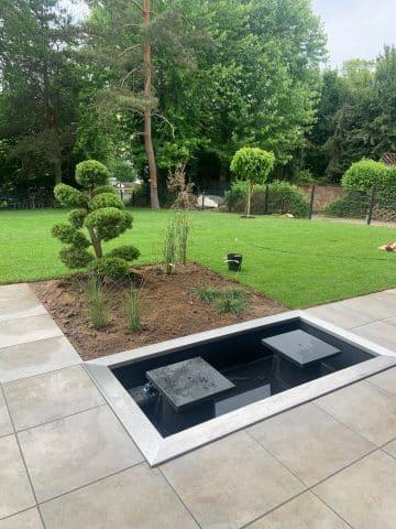 Teich mit Springbrunnen mit Blick auf den Garten