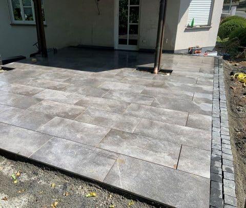 Terrasse mit großen Platten ist mit Pflastersteinen umrandet