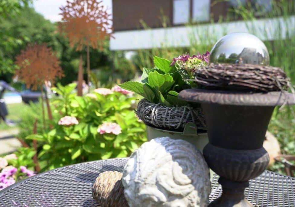 Dekoration auf Tisch mit bepflanztem Garten im Hintergrund