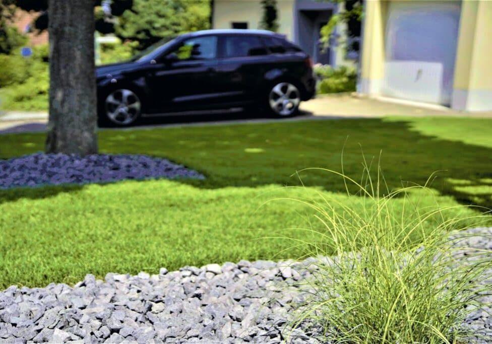 Rasen mit Auto und Garage im Hintergrund